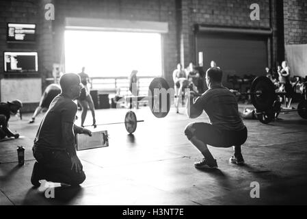 Trainer observing cross training athlete doing squats with barbell in gym - Stock Photo