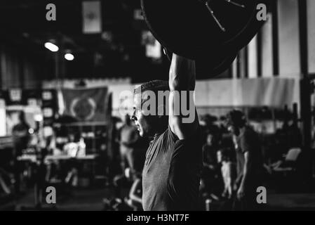 Cross training athlete lifting barbell in gym - Stock Photo