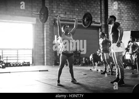 Trainer observing cross training athlete lifting barbell in gym - Stock Photo
