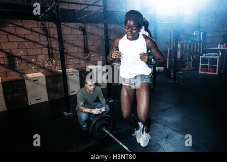 Trainer observing cross training athlete jumping over barbell in gym - Stock Photo