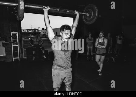 Cross training athlete observing man lifting barbell in gym - Stock Photo