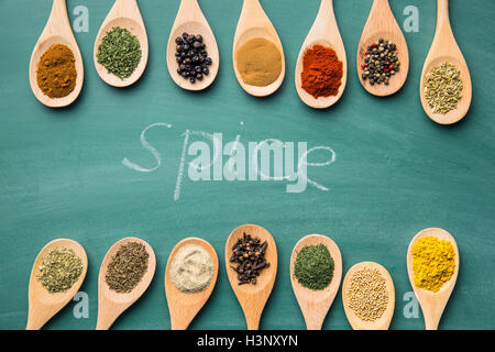 Various spices in wooden spoons on chalkboard. Top view. - Stock Photo