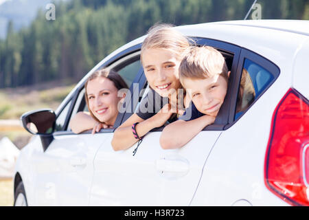 Happy young woman and her children sitting in a car and look out from windows. Family travel background image - Stock Photo