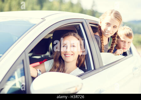 Happy young woman and her children sitting in a car and look out from windows. Family travel warm color toned image - Stock Photo