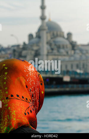 Muslim women, wearing a orange head kerchief, with the mosque in front of her - Stockfoto