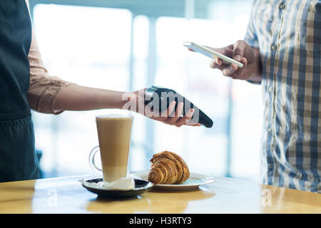 Man paying bill through smartphone using NFC technology - Stock Photo