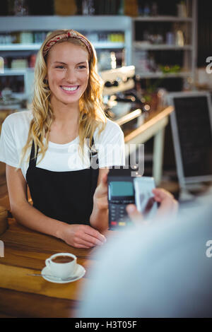 Customer paying bill through smartphone using NFC technology - Stock Photo
