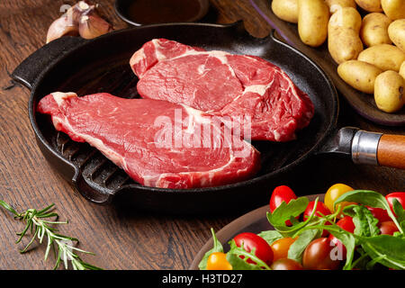 Raw beef steak on grill pan, potatoes, spices and tomatoes on wooden table - Stock Photo