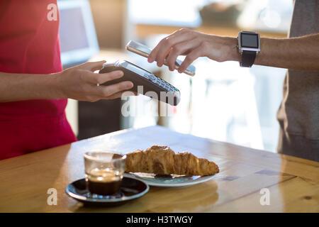 Man paying bill through smartphone using NFC technology - Stock Photo