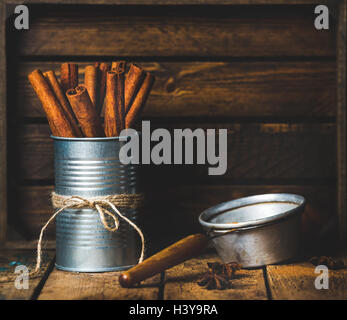 Cinnamon sticks in can tied with rope, anise and sieve - Stock Photo
