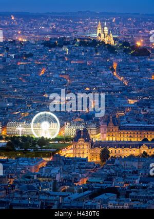 Aerial view of Paris rooftops at dusk, including The Louvre, and Sacre Coeur in Montmartre. Blue hour in the City - Stock Photo