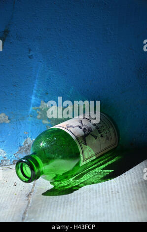An old green glass  bottle labelled with arsenic poison and a skull and bone sign lies on the ground. - Stock Photo