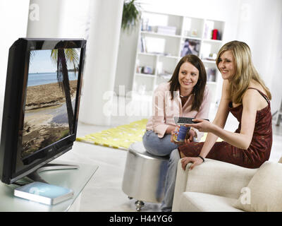 Sitting rooms, girls, watch TV, pass Apple TV, happy, leisure time, leisure activities, consumer electronics, TV, - Stock Photo