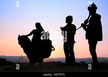 Sunset, silhouette of a woman dancing a traditional dance with two musicians, Pushkar, Rajasthan, India - Stock Photo