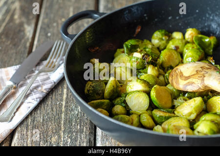 Pan-fried Brussels sprouts in cast-iron frying pan on wooden table - Stock Photo