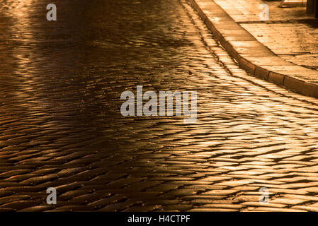 wet street curve with gutter and cobblestones illuminated by night - Stock Photo