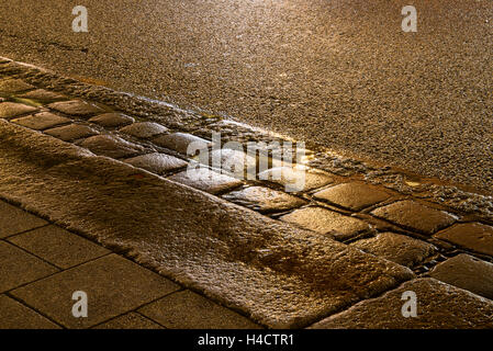 gutter with wet cobblestone illuminated in the night - Stock Photo