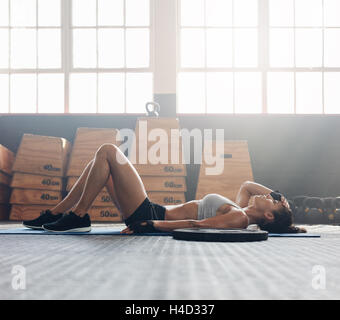 Young woman lying on her back at the gym after her workout. Fitness woman relaxing after exercise session. - Stock Photo