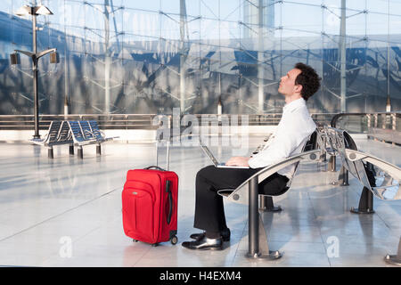Businessman imagining ideas while waiting in airport lounge - Stock Photo