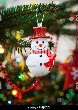 Christmas decoration snowman on xmas tree and garland background - Stock Photo