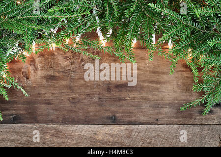 Christmas tree pine branches and decorative lights over a rustic background of barn wood. Image shot from overhead. - Stock Photo