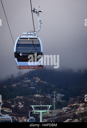 Cable car descending from Monte to Funchal as cloud hangs over Monte hillside - Stock Photo
