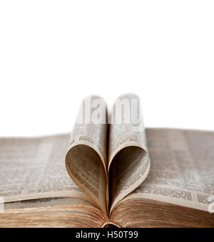 An old Bible opened with deliberate focus on the edges of the heart-shaped folded pages and copy space. Shallow - Stock Photo