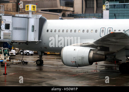 An airplane connected to a jet bridge being serviced at an airport before its next scheduled flight. - Stock Photo