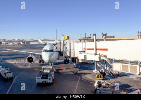 A passenger plane connected to a jet bridge being serviced by at airport gate. - Stock Photo
