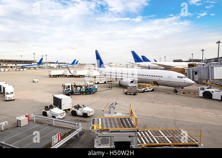 A fleet of commercial aircrafts being serviced at the terminal of an international airport. - Stock Photo