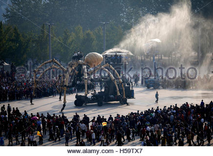People watch a mechanical installation named 'The Spider'  emit water vapor during the Long Ma performance in front - Stock Photo