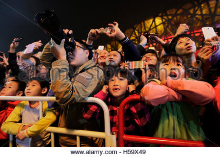 Spectators react as they watch a mechanical installation named 'Long Ma' breathe fire during the Long Ma performance - Stock Photo