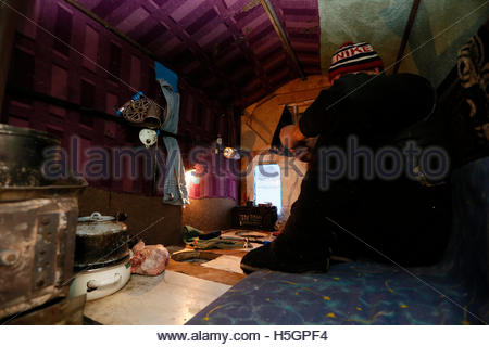 Fisherman Alexander Romantsov sits inside his plywood lodge, placed on the frozen surface of the Yenisei River over - Stock Photo