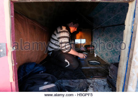 A man fishes as he sits inside his plywood lodge, placed on the frozen surface of the Yenisei River over an ice - Stock Photo