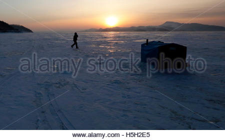 A fisherman walks past a plywood lodge, placed on the frozen surface of the Yenisei River over an ice hole for fishing - Stock Photo