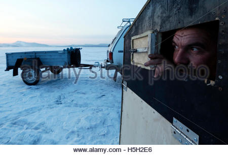 Fisherman Alexander Romantsov looks out of the window of his plywood lodge, placed on the frozen surface of the - Stock Photo