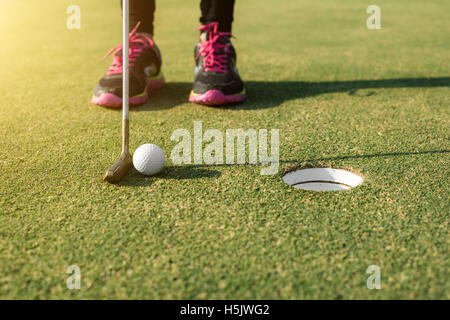 Golf player at the putting green putting golf ball into a hole. Golf sport concept. - Stock Photo