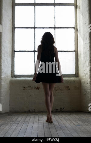 Young woman in short black dress standing by the window - Stock Photo