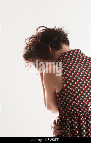 Rear view of a young woman head in hands against a white background - Stock Photo