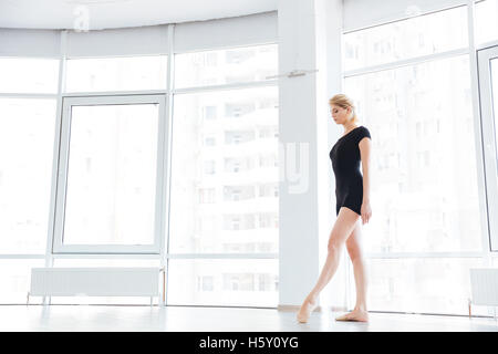 Young attractive female ballet dancer is smiling and standing in the pose - Stock Photo