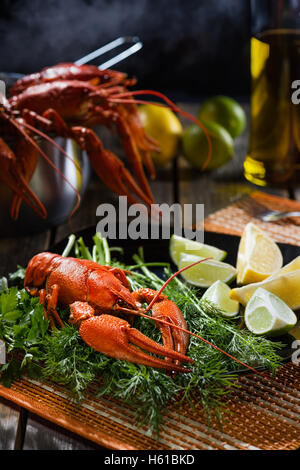 Boiled crayfish with fresh greens and a citrus on  black plate in style  rustic - Stock Photo