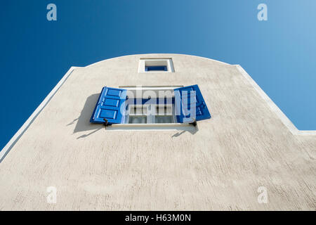Blue shutters on the window of a white washed building against blue sky on Santorini, Greece. - Stock Photo