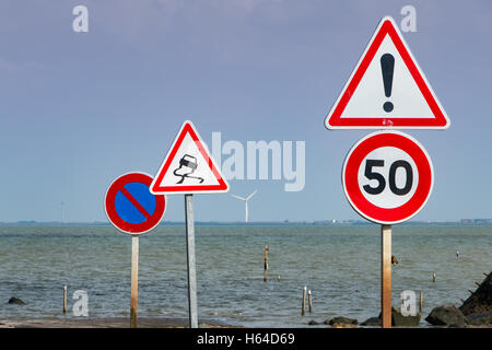 together of road signs for warning next to sea - Stock Photo