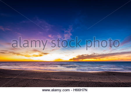 Pink clouds reflected in the calm ocean at sunset - Stock Photo