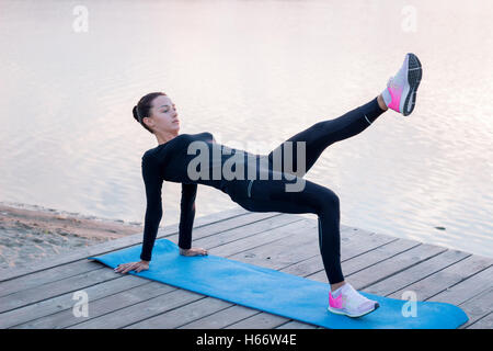Young pretty fitness woman exercises on pier during morning training workout - Stockfoto