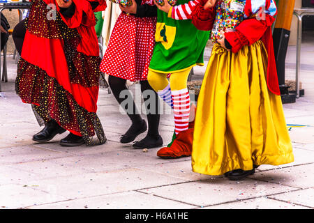 Carnival season: children walking together on the street dressed in colorful carnival costumes - Stock Photo