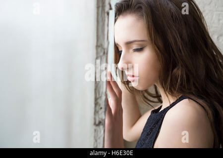 Sad young woman standing by the window - Stock Photo