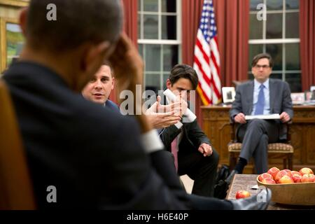 U.S. President Barack Obama listens to senior advisors during a meeting in the White House Oval Office January 30, - Stock Photo