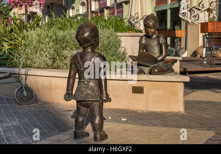 Children Playing, bronze sculpture created by Rita Soros and Eva Szabo in 2010, on Ady Endre utca in Kaposvar, Hungary - Stock Photo