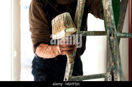 Painter on a ladder holding wall painting brush in his hand. - Stock Photo